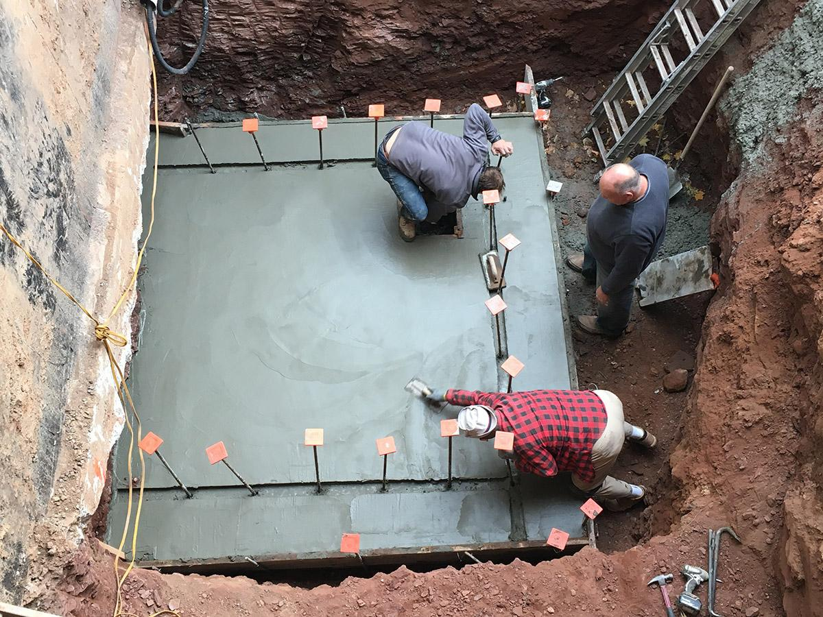 Masons pour concrete slab for elevator shaft